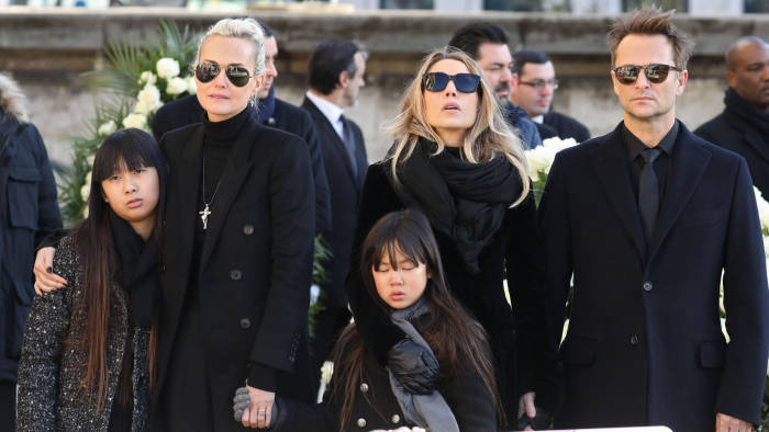 Son of late French singer Johnny Hallyday David Hallyday (1st-R), daughter Laura Smet (2nd R), Johnny's wife Laeticia (4th-R), their daughters Jade (5th-R) and Joy (3rd-R) stand by the coffin outside the Eglise de la Madeleine (Madeleine Church) at the start of the funeral ceremony for their late father and husband on December 9, 2017 in Paris. French music icon Johnny Hallyday died on December 6, 2017 aged 74 after a battle with lung cancer, plunging the country into mourning for a national treasure whose soft rock lit up the lives of three generations. / AFP PHOTO / POOL / ludovic MARIN (Photo credit should read LUDOVIC MARIN/AFP via Getty Images)