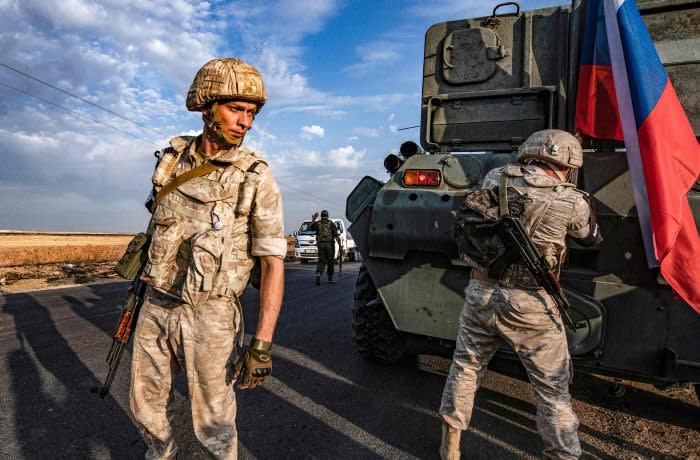 TOPSHOT - Russian military police members stand outside an armoured vehicle along a road in the countryside near the northeastern Syrian town of Amuda in Hasakeh province on October 24, 2019, as part of a joint patrol between Russian forces and Syrian Kurdish Asayish internal security forces near the border with Turkey. - Russian forces have started patrols along the flashpoint frontier, filling the vacuum left by a US troop withdrawal that effectively returned a third of the country to the Moscow-backed regime of President Bashar al-Assad. (Photo by Delil SOULEIMAN / AFP) (Photo by DELIL SOULEIMAN/AFP via Getty Images)
