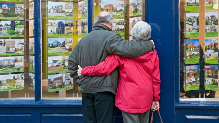 DH4RKB Older couple looking in estate agent's window York North Yorkshire England UK United Kingdom GB Great Britain