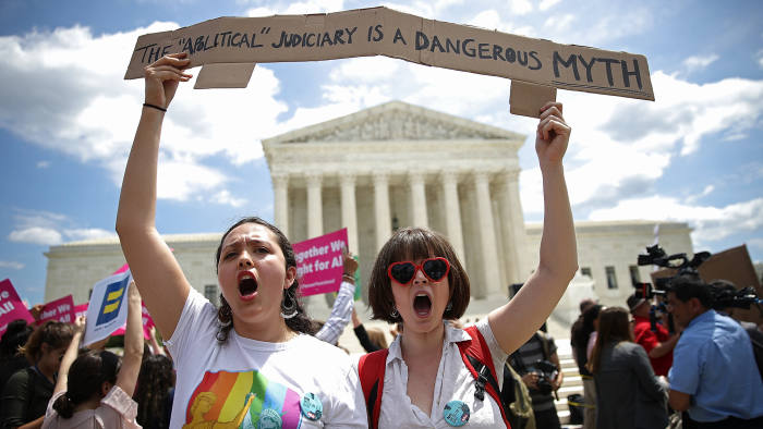 WASHINGTON, DC - JUNE 26: Protesters Celina Scott-Buechler (R) and Lisset Pino (L) demonstrate against U.S. President Trump's travel ban as protesters gather outside the U.S. Supreme Court following a court issued immigration ruling June 26, 2018 in Washington, DC. The court issued a 5-4 ruling upholding U.S. President Donald Trump's travel ban imposing limits on travel from several primarily Muslim nations. (Photo by Win McNamee/Getty Images)
