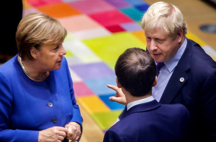 British Prime Minister Boris Johnson (R), French President Emmanuel Macron (C) and German Chancellor Angela Merkel (L) speak upon their arrival for a round table meeting as part of a European Union summit at European Union Headquarters in Brussels on October 17, 2019. - Britain and the European Union reached a new divorce deal on October 17, 2019 that could allow Brexit on October 31, but faced immediate opposition among MPs in London -- who can still block it. (Photo by Olivier Matthys / POOL / AFP) (Photo by OLIVIER MATTHYS/POOL/AFP via Getty Images)