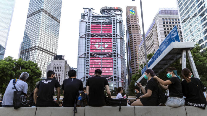 Pro-democracy demonstrators sit on a road divider during a protest in July near the HSBC building in Hong Kong