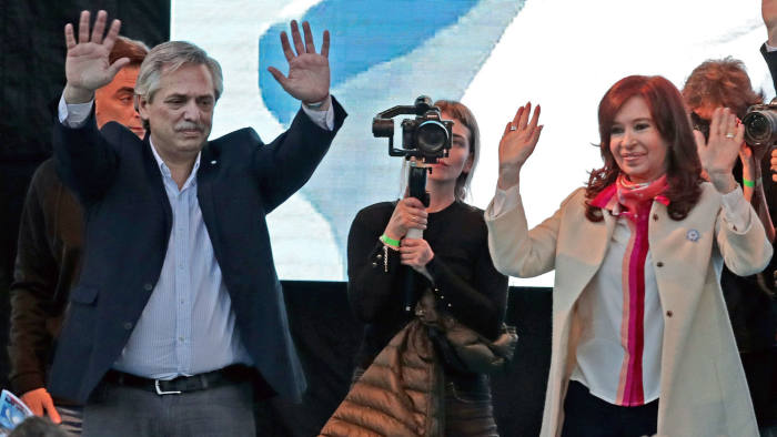 Former Argentine President and current Senator Cristina Fernandez de Kirchner (R) and her former Chief of Cabinet Alberto Fernandez wave to supporters during the reopening of a sports venue under the name