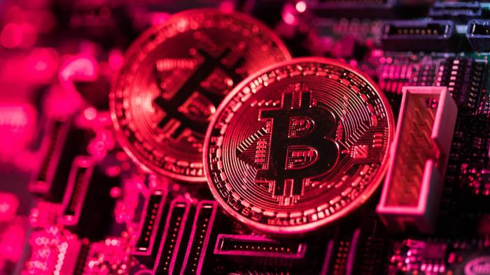 Two coins representing Bitcoin cryptocurrency sit on a computer circuit board in this arranged photograph in London, U.K., on Tuesday, Feb. 6, 2018. Cryptocurrencies tracked by Coinmarketcap.com have lost more than $500 billion of market value since early January as governments clamped down, credit-card issuers halted purchases and investors grew increasingly concerned that last year's meteoric rise in digital assets was unjustified. Photographer: Chris Ratcliffe/Bloomberg