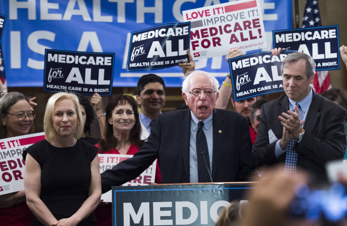 "UNITED STATES - APRIL 10: From left, Sens. Kirsten Gillibrand, D-N.Y., Bernie Sanders, I-Vt., and Jeff Merkley, D-Ore., conduct an event to introduce the ""Medicare for All Act of 2019"" in Dirksen Building on Wednesday, April 10, 2019. (Photo By Tom Williams/CQ Roll Call)"