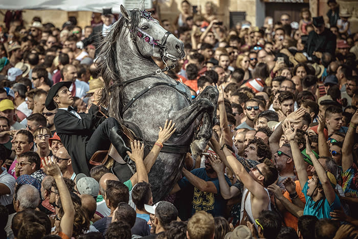 People gather around a horse rider as he rears up during the 'Caragol des Born' traditional parade on the eve of Saint-Jean-Baptiste Day in Ciutadella de Menorca, Spain, 23 June 2018. Photo: Matthias Oesterle/ZUMA Wire/dpa