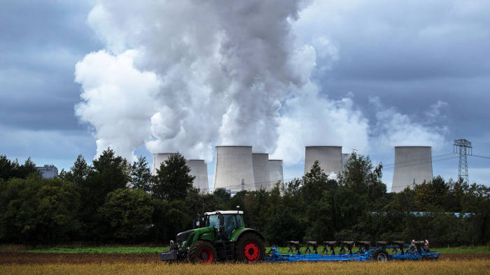 A tractor ploughs farmland as emissions rise from cooling towers beyond at the Jaenschwalde lignite fired power plant, operated by Lausitz Energie Bergbau AG (LEAG), in Teichland, Germany, on Monday, Sept. 16, 2019. Policies being hammered out in Germany to slash carbon emissions may cost 40 billion euros ($44 billion) over the next four years, underscoring the wide scope of Chancellor Angela Merkels plans to boost climate protection. Photographer: Krisztian Bocsi/Bloomberg