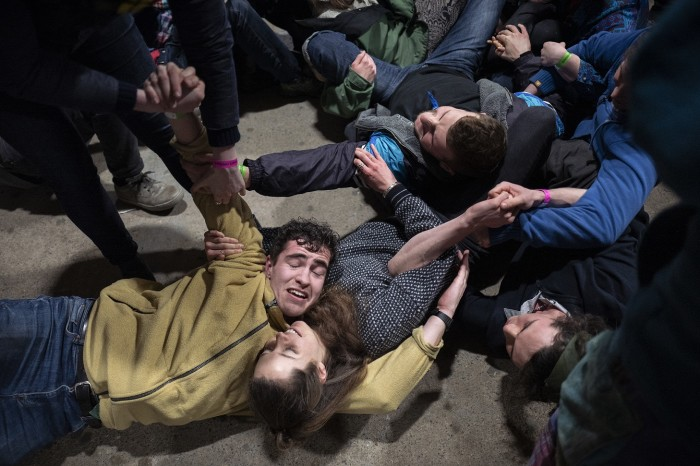 Extinction Rebellion volunteers roleplay protesters locking arms and police trying to haul them away