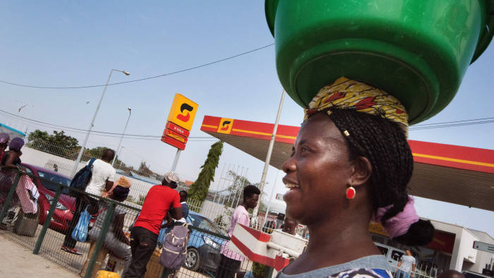 """A fruit vendor carries her wares past a petrol station of Sonangol, the national fuel society of Angola, in Luanda on November 13, 2018. - One year after the election of President Joao Lourenco, the oil-rich nation is still waiting for the economic """"miracle"""" that he promised on the campaign trail. In a country scarred by prolonged war -- and where the economic benefits of an oil-fuelled boom have not always trickled down to the mass population -- entrenched poverty remains the norm for nearly half the population. (Photo by Rodger BOSCH / AFP) (Photo credit should read RODGER BOSCH/AFP/Getty Images)"""