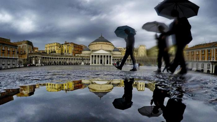 Mandatory Credit: Photo by CIRO FUSCO/EPA-EFE/REX/Shutterstock (9940093b) Pedestrians are reflected in a puddle as they protect themselves from the pouring rain with umbrellas while walking in downtown Naples, southern Italy, 22 October 2018. Heavy rains had battered Italy from north to south on 21 October evening with even hailstorms been reported in Rome. Seen in background is the neo-classical Royal Palace at the Piazza del Plebiscito. Bad weather in Naples, Italy - 22 Oct 2018