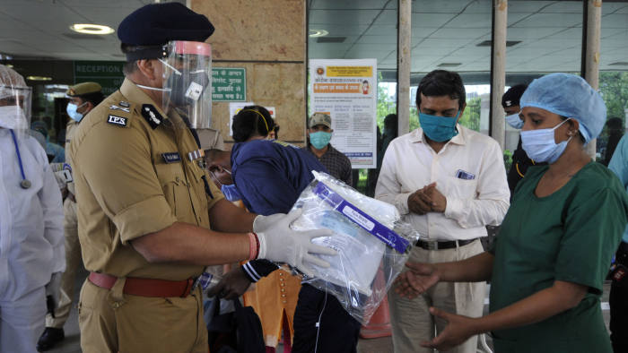 NOIDA, INDIA - APRIL 30: Police commissioner Alok Singh distributes the safety kits to the cleaning workers of district hospital, during a nationwide lockdown due to coronavirus pandemic, at Sector 30, on April 30, 2020 in Noida, India. (Photo by Sunil Ghosh/Hindustan Times via Getty Images)