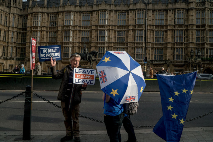 A pro-Leave (the EU) demonstrator talks to a pro-Remain (in the EU) demonstrator outside Parliament.