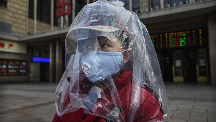 BEIJING, CHINA - FEBRUARY 12: A Chinese boy is covered in a plastic bag for protection as he arrives from a train at Beijing Station on February 12, 2020 in Beijing, China. The number of cases of a deadly new coronavirus rose to more than 44000 in mainland China Wednesday, days after the World Health Organization (WHO) declared the outbreak a global public health emergency. China continued to lock down the city of Wuhan in an effort to contain the spread of the pneumonia-like disease which medicals experts have confirmed can be passed from human to human. In an unprecedented move, Chinese authorities have put travel restrictions on the city which is the epicentre of the virus and municipalities in other parts of the country affecting tens of millions of people. The number of those who have died from the virus in China climbed to over 1100 on Wednesday, mostly in Hubei province, and cases have been reported in other countries including the United States, Canada, Australia, Japan, South Korea, India, the United Kingdom, Germany, France and several others. The World Health Organization has warned all governments to be on alert and screening has been stepped up at airports around the world. Some countries, including the United States, have put restrictions on Chinese travellers entering and advised their citizens against travel to China. (Photo by Kevin Frayer/Getty Images)