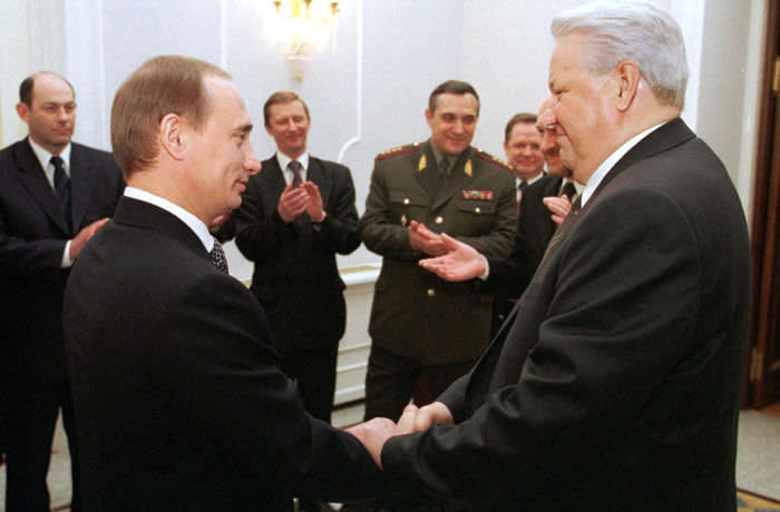 MOSCOW, RUSSIA - DECEMBER 31: Russian President Boris Yeltsin (R) shakes hands with Prime Minister Vladimir Putin (L) during a farewell ceremony in Kremlin in Moscow, as members of the Presidential administration and the government look on and applaud 31 December 1999. Boris Yeltsin earlier today announced that he was resigning immediately and that Vladimir Putin, according to the Russian Constitution, would run the country as acting President until presidential elections in March 2000. (Photo credit should read AFP/AFP via Getty Images)