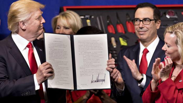 U.S. President Donald Trump, center, left, displays a signed executive order during an event at Snap-On Tools Corp. headquarters in Kenosha, Wisconsin, U.S., on Tuesday, April 18, 2017. Trump signed executive orders pushing for U.S. government to