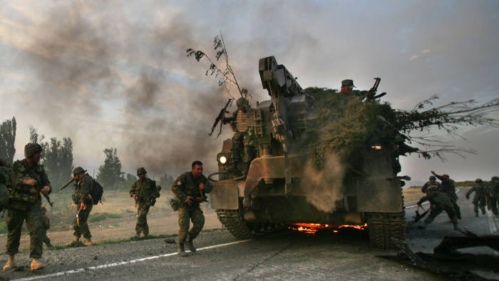 GORI, GEORGIA - AUGUST 11: (ISRAEL OUT)  Georgian soldiers escape their burning armoured vehicle on the road to Tbilisi on August 11, 2008 just outside Gori, Georgia. Russia called today for Georgian forces to surrender in the separatist enclave of Abkhazia after Georgia called a ceasefire and withdrew their forces from South Ossetia, leaving Russian forces now firmly in control in the disputed region.  (Photo by Uriel Sinai/Getty Images)
