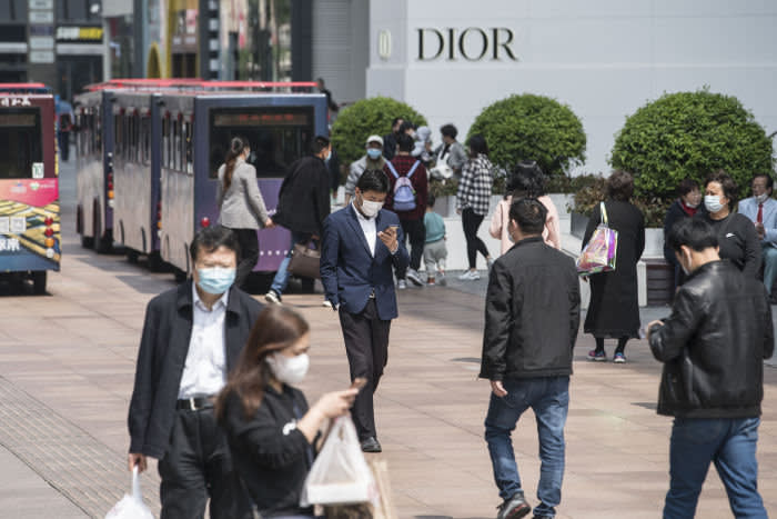 Pedestrians wearing protective masks walk along Nanjing Road in Shanghai, China, on Monday, April 20, 2020. Chinese banks lowered borrowing costs and the governmentpromisedto sell another 1 trillion yuan ($141.3 billion) in bonds to pay for stimulus spending after the economy had its first contraction in decades due to the coronavirus outbreak. Photographer: Qilai Shen/Bloomberg