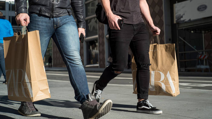 Pedestrians carry shooting bags from Zara fashion store, operated by Inditex SA, in San Francisco, California, U.S., on Thursday, Dec. 26, 2019. Confidence among U.S. consumers advanced to a nine-week high on greater optimism about the economy and brighter views of personal finances and the buying climate. Photographer: David Paul Morris/Bloomberg