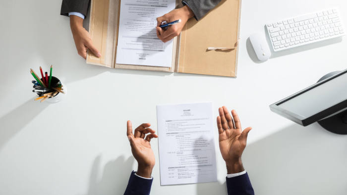 M6JJW3 Elevated View Of Businessperson And Candidates Hand With Resume On White Desk