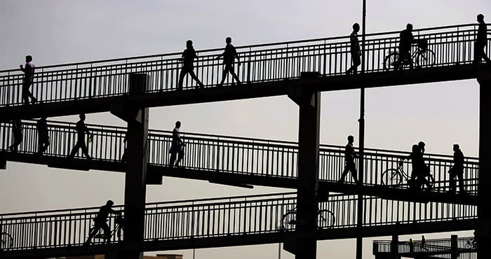 TOPSHOT - Asian workers working in Dubai are seen waling at a footbridge on February 14, 2018. / AFP PHOTO / KARIM SAHIBKARIM SAHIB/AFP/Getty Images