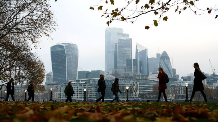 People walk through autumnal leaves in front of the financial district in London, Britain, November 21, 2019. REUTERS/Hannah McKay - RC2LFD93GG0G