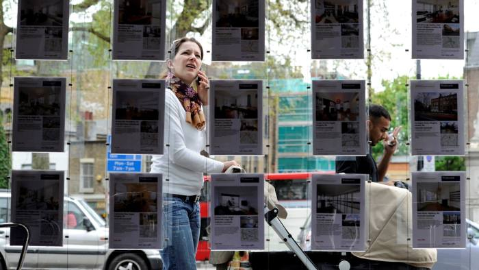 A woman stops to look in the window of an estate agent in Islington, north London, Britain, April 29, 2010. REUTERS/Paul Hackett/File Photo - D1AEUGXKCZAB