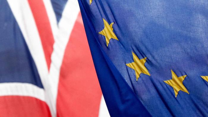 A British Union flag, commonly known as a Union Jack, left, flies next to a European Union (EU) flag, in London, U.K., on Wednesday, Feb. 17, 2016. German Chancellor Angela Merkel threw her political muscle behind the push for a deal to keep the U.K. in the European Union as diplomats worked to bridge the remaining differences between its members.Photographer: Chris Ratcliffe/Bloomberg
