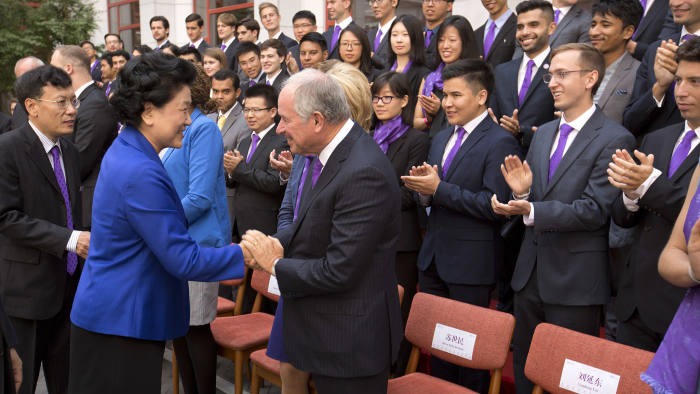 In this Sept. 10, 2016, photo, Chinese Vice Premier Liu Yandong, second from left, shakes hands with Blackstone Group co-founder Stephen Schwarzman as she arrives for a group photo with the Schwarzman Scholars before a ceremony to officially open the scholar program at Tsinghua University in Beijing. A study program at an elite Chinese university that was inspired by the prestigious Rhodes Scholarship launched its second year Friday, Sept. 8, 2017 with an endowment of more than $500 million and a considerable rise in applications. (AP Photo/Mark Schiefelbein)