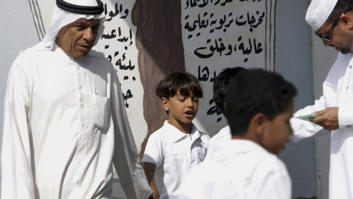 Parents wait to pick up their children as boys head out of the gates of a primary school in the western village of Karzakan, Bahrain, on Sunday, Oct. 30, 2011. As of Oct. 31, according to the U.N. Population Fund, there will be 7 billion people sharing Earth's land and resources. (AP Photo/Hasan Jamali)