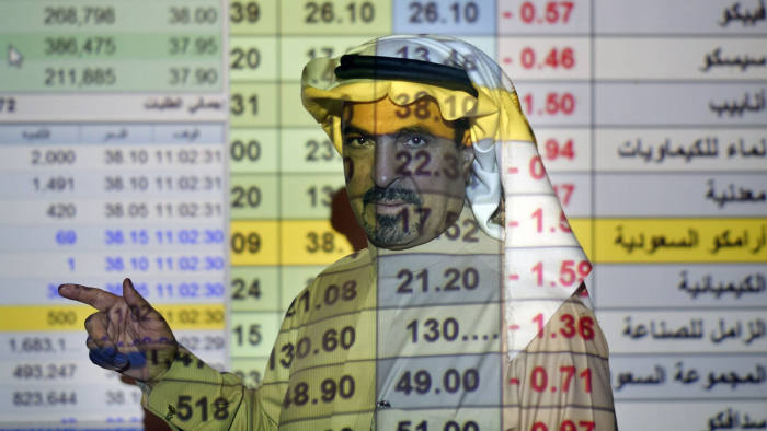 A trader talks to others in front of a screen displaying Saudi stock market values at the Arab National Bank in Riyadh, Saudi Arabia, Thursday, Dec. 12, 2019. Shares in Saudi Aramco gained on the second day of trading Thursday, propelling the oil and gas company to a more than $2 trillion valuation where it holds the title of the world's most valuable listed company. (AP Photo/Amr Nabil)