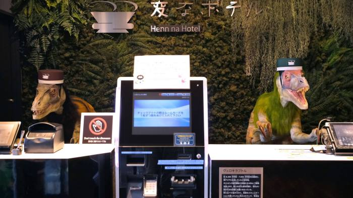 "A pair of robot dinosaurs wearing bellboy hats welcome guests from the front desk at the Henn-na Hotel in Urayasu, suburban Tokyo on August 31, 2018. - The reception at the Henn-na Hotel east of Tokyo is eeriely quiet until customers near the robot dinosaurs manning front desk. Their sensors detect motion and they bellow: ""Welcome."" It might be about the weirdest check-in experience possible, but that's exactly the point at the Henn-na (""Weird"") chain, which bills itself as offering the world's first hotels staffed by robots. (Photo by Kazuhiro NOGI / AFP) (Photo credit should read KAZUHIRO NOGI/AFP/Getty Images)"