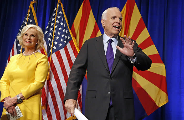 FILE - In this Nov. 8, 2016, file photo, Sen. John McCain, R-Ariz., right, waves to supporters at his victory party as wife Cindy McCain, left, joins him on stage as he announces his victory over Democratic challenger Rep. Ann Kirkpatrick in Phoenix. (AP Photo/Ross D. Franklin, File)
