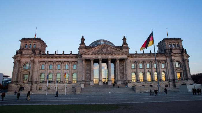 Pedestrians walk outside the Reichstag building, which houses the Bundestag federal parliament, as German national flags fly in Berlin, Germany, on Sunday, Nov. 13, 2016. Chancellor Angela Merkel gave ground to her coalition partner and agreed to support Foreign Minister Frank-Walter Steinmeier as the next German president, laying the ground for a resumption of the two parties' alliance after next year's federal election. Photographer: Krisztian Bocsi/Bloomberg