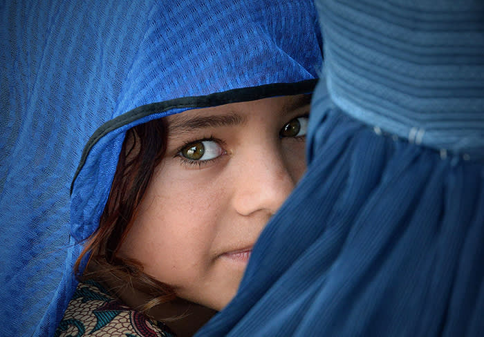 TOPSHOT - An Afghan woman carries her girl during the visit of the United Nations High Commissioner for Refugees, Filippo Grandi (unseen) at the Azakhel Voluntary Repatriation Centre in Nowshera on September 8, 2018. - The United Nations High Commissioner for Refugees Filippo Grandi is on an official three-day visit to Islamabad. (Photo by ABDUL MAJEED / AFP)ABDUL MAJEED/AFP/Getty Images