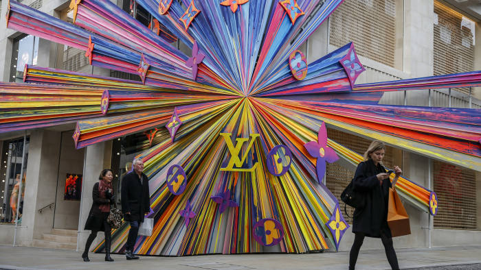 """Shoppers pass colorful store-front design on the front of a Louis Vuitton store, operated by LVMH Moet Hennessy Louis Vuitton SE, on New Bond Street in Mayfair, London, United Kingdom, on Thursday, Oct. 31, 2019. In the lead-up to the vote, """"both Labour and the Conservatives are expected to come out with pretty punchy views on tax, innovation and public spending, which could have significant implications for both corporates and consumers,""""Emma Wall, head of investment analysis at stockbroker Hargreaves Lansdown Plc, said by email.Photographer: Hollie Adams/Bloomberg"""