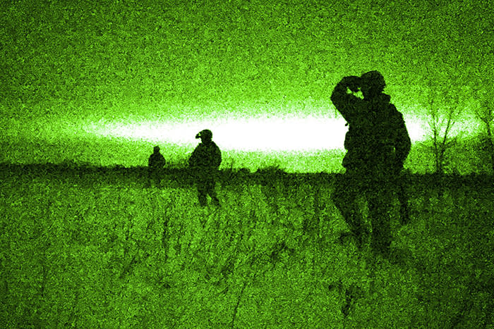 Airmen, shown through a night vision device, hike in a tactical formation during a nighttime winter mobilization exercise in Kansasville, Wisconsin, U.S. February 10, 2018. Picture taken February 10, 2018. Air National Guard/Staff Sgt. Morgan R. Lipinski/Handout via REUTERS ATTENTION EDITORS - THIS IMAGE WAS PROVIDED BY A THIRD PARTY. TPX IMAGES OF THE DAY