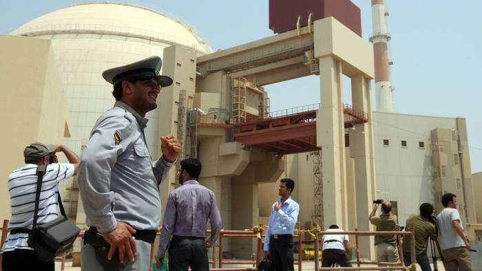 An Iranian security man stands next to journalists outside the reactor building at the Russian-built Bushehr nuclear power plant in southern Iran on August 21, 2010 during a ceremony initiating the transfer of Russia-supplied fuel to the facility after more than three decades of delay. AFP PHOTO/ATTA KENARE (Photo credit should read ATTA KENARE/AFP/Getty Images)