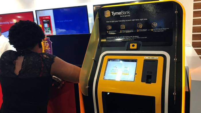 A woman stands next to a TymeBank client onboarding kiosk in Johannesburg, South Africa, November 28, 2018. Picture taken November 28, 2018. REUTERS/Tiisetso Motsoeneng - RC17CD8F5080