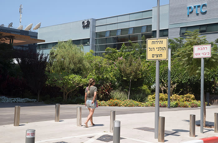 An Israeli woman walks in front of the building housing the Israeli NSO group, on August 28, 2016, in Herzliya, near Tel Aviv. Apple iPhone owners, earlier in the week, were urged to install a quickly released security update after a sophisticated attack on an Emirati dissident exposed vulnerabilities targeted by cyber arms dealers. Lookout and Citizen Lab worked with Apple on an iOS patch to defend against what was called