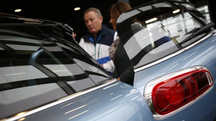 Shoppers view a Bayerische Motoren Werke AG (BMW) MINI vehicle inside the showroom of a car dealership in Louisville, Kentucky, U.S., on Friday, Nov. 25, 2016. Ward's Automotive Group is scheduled to release U.S. monthly total and domestic auto sales on December 1. Photographer: Luke Sharrett/Bloomberg