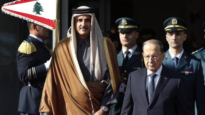 Qatar's Emir Sheikh Tamim bin Hamad Al Thani, left, walks with Lebanese President Michel Aoun, right, as they review the honor guard at the Rafik Hariri international airport in Beirut, Lebanon, Sunday, Jan. 20, 2019. The ruler of the wealthy Gulf state of Qatar has arrived in Beirut to attend an Arab economic summit that has been marred by divisions over readmitting Syria to the Arab League. (AP Photo/Hussein Malla)