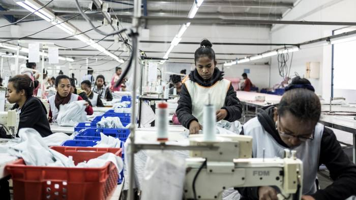 Workers sew garments at a textile manufacturing facility in Antananarivo, Madagascar, on Wednesday, July 25, 2018. Madagascar's exports are projected to continue to boom in 2018-19, with strong demand for textiles and essential oils produced in the free trade zone, as well as cloves and vanilla, according to the African Development Bank Group. Photographer: Miora Rajaonary/Bloomberg