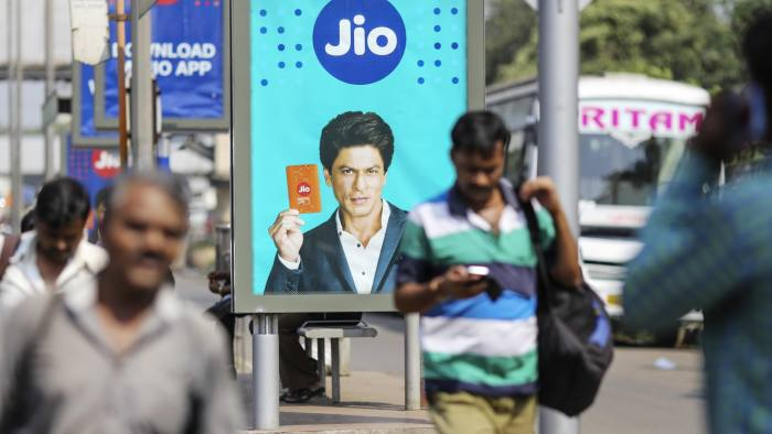 An advertisement featuring Bollywood actor Shah Rukh Khan for Reliance Jio, the mobile network of Reliance Industries Ltd., is displayed at a bus stop in Mumbai, India, on Monday, Oct. 24, 2016. Mukesh Ambani's Reliance Industries began offering mobile services last month under the Jio brand. Photographer: Dhiraj Singh/Bloomberg