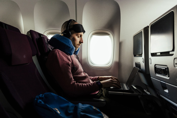 Journalist Simon Usbourne onboard a Qatar Airways flight at London Heathrow. Photographed by Greg Funnell for the Financial Times, 8th March 2018.