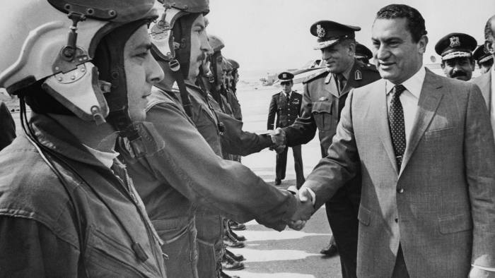 Egyptian President Hosni Mubarak (R) shakes hands with jet pilots during a visit to a military dependency, 29 April 1991. Mubarak joined the Air Force Academy in 1950 and received instruction in the Soviet Union, moving up the chain of command from pilot, to instructor to squadron leader to base commander. He was appointed Director of the Air Force Academy and Chief of Staff of the Egyptian Air Force during the War of Attrition between Egypt and Israel (1967-72) and by 1973 was promoted to the rank of Air Chief Marshal. In April 1975, he was appointed Vice-President of Egypt. Mubarak came to office as Egypt?s fourth president after late President Anwar Sadat was slained by a group of military Islamist fundamentalists with allegiance to the Al-Jihad during a military parade 06 October 1981 and has remained in power ever since, being re-elected five times. AFP PHOTO/- (Photo credit should read AFP PHOTO/AFP via Getty Images)