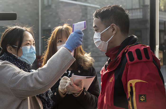 A member of the media has his temperature checked before proceeding to a tour of a factory operated by Dasheng Health Products Manufacturing Co. in Shanghai, China, on Friday, Jan. 31, 2020. People across the globe are stockpiling facial masks to protect themselves from the new coronavirus, depleting online malls and store shelves from California to Beijing. Photographer: Qilai Shen/Bloomberg