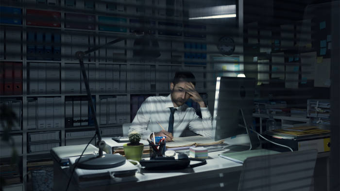 Young business executive working in the office late at night, deadlines and overtime work concept
