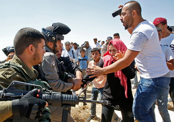 Palestinian protesters and Israeli soldiers scuffle during clashes to disperse them from a school site being demolished and relocated in another area, in the village of Yatta, south of the West Bank city of Hebron on July 11, 2018. / AFP PHOTO / HAZEM BADERHAZEM BADER/AFP/Getty Images