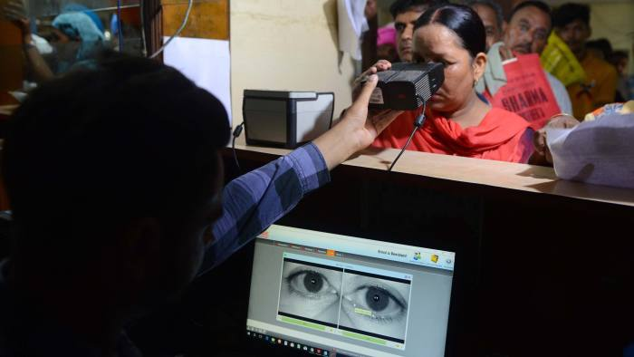 This photo taken on July 17, 2018 shows an Indian woman looking through an optical biometric reader that which scans an individual's iris patterns, during registration for Aadhaar cards (or unique identifier [UID] cards) in Amritsar. - India's top court on September 26 upheld the government's Aadhaar scheme, the world's largest biometric database, but imposed new restrictions on how the personal details of more than one billions citizens in the system can be used. (Photo by NARINDER NANU / AFP) (Photo credit should read NARINDER NANU/AFP/Getty Images)