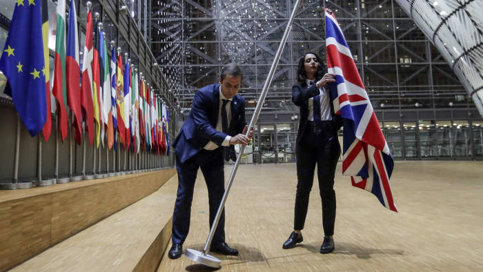 TOPSHOT - EU Council staff members remove the United Kingdom's flag from the European Council building in Brussels on Brexit Day, January 31, 2020. - Britain leaves the European Union at 2300 GMT on January 31, 2020, 43 months after the country voted in a June 2016 referendum to leave the block. The withdrawal from the union ends more than four decades of economic, political and legal integration with its closest neighbours. (Photo by OLIVIER HOSLET / POOL / AFP) (Photo by OLIVIER HOSLET/POOL/AFP via Getty Images)